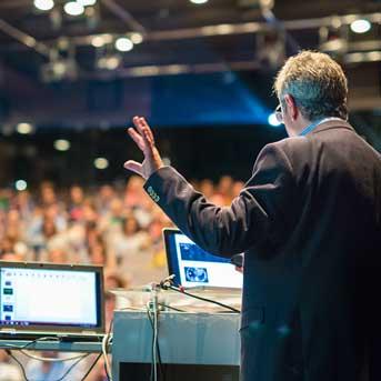 Speaker at medical presentation using AV equipment for PowerPoint.